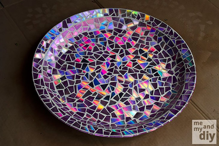 Base de la pileta de pájaros cubierta de mosaicos hechos por piezas de CDs