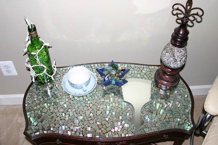 Mesa decorada con piezas de CD y objetos sobre ellas