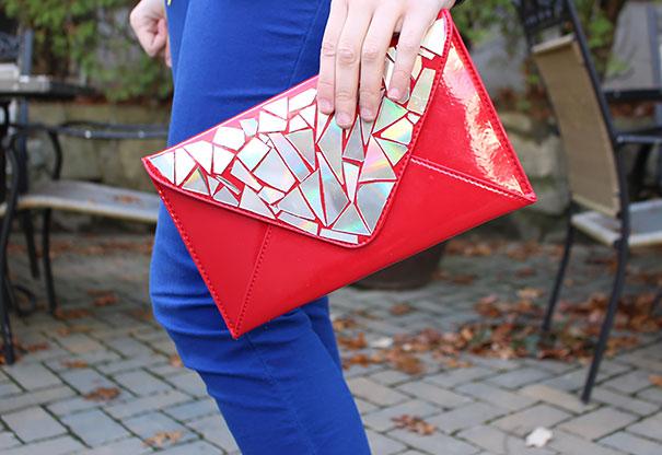 Una mano sosteniendo una cartera adornada con piezas de CD