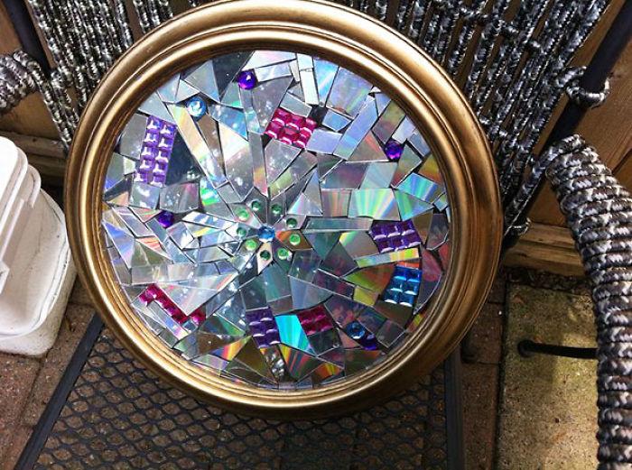 Adorno de pared en forma circular con pequeñas piezas de CDs