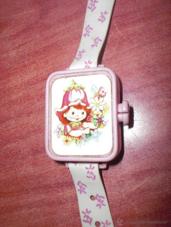 Un reloj con una muñequita en su parte delantera