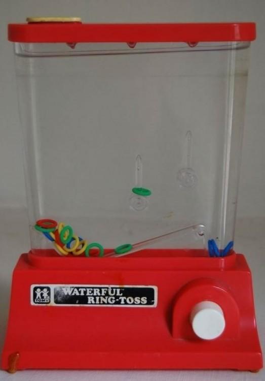 Un juguete en color rojo con una parte transparente donde debes introducir unos círculos de colores en unos picos