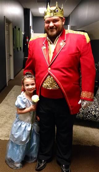 Hombre disfrazado de príncipe y niña de princesa