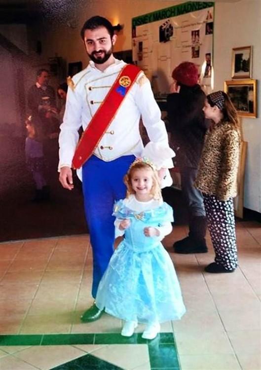 Niña con disfraz de princesa y hombre de príncipe en el cine
