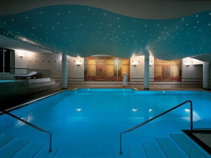 Piscina de un spa con un techo en color verde azulado con pequeños puntos que simulan ser estrellas y son unas pequeñas luces