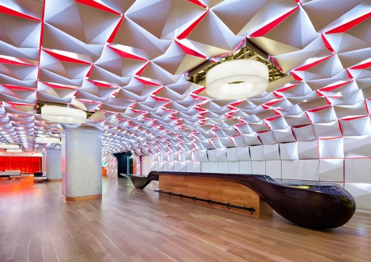 Sala con un techo en forma de cuadros en color blanco con rojo que se va formando poco a poco desde las paredes