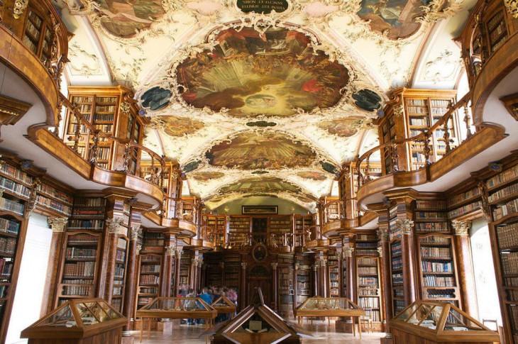 Biblioteca con un estilo clásico y en el techo diseños con formas de flores y dibujos de estilo romano en su interior