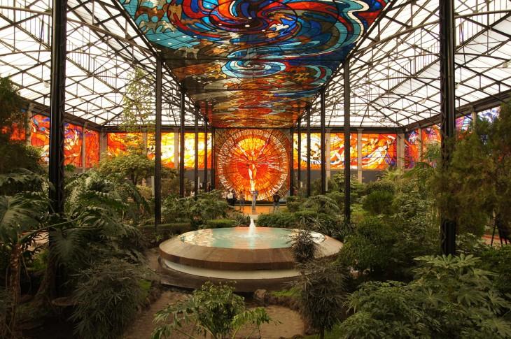 Un lugar público en Toluca con áreas verdes y una fuente al centro en su techo una fila de formas circulares de diferentes colores