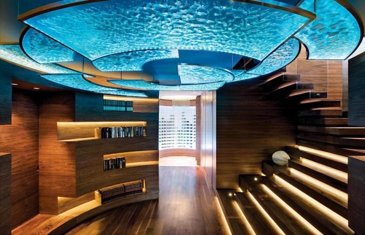 Recibidor de una casa con unos libros en una de sus paredes frente a unas escaleras y su techo con vidrio en color azul que simula ser de agua