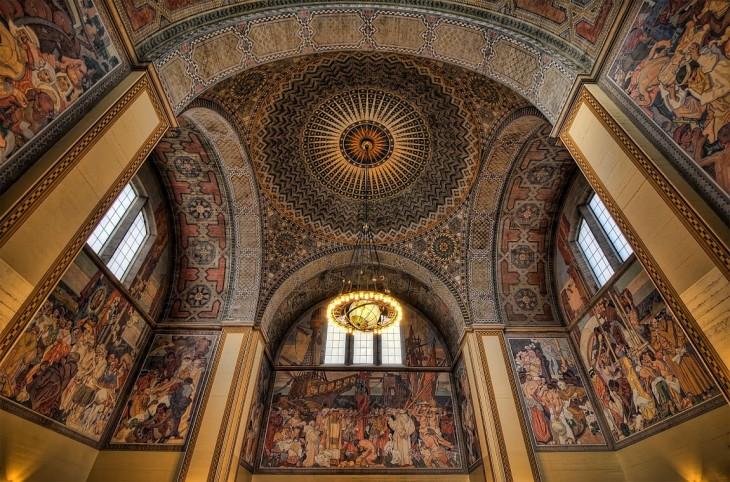 Biblioteca con diseños de personas romanas en sus paredes, arcos y su techo con circulo de figuras en colores opacos