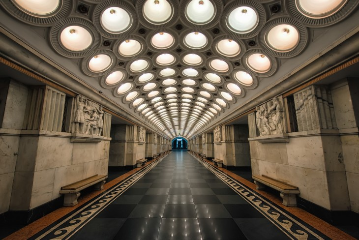 Pasillo de una estación del metro con un techo de pequeños círculos con focos en el centro