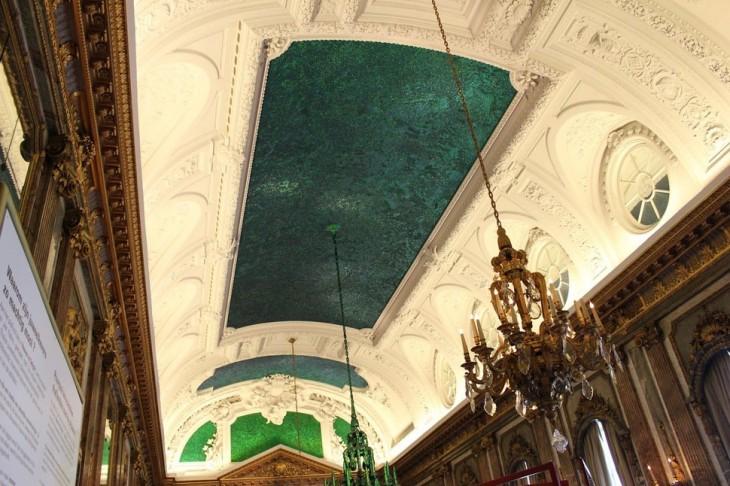 Salón de los espejos en Bélgica con un techo con estilo de iglesia y espacios en un color verde obscuro muy elegante
