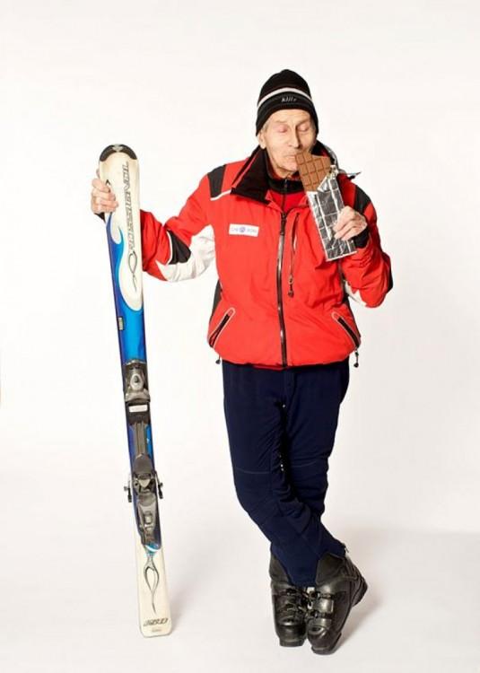 Esquiador de la tercera edad con un chocolate en la mano simulando que se lo esta comiendo
