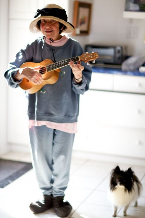 Mujer anciana tocando la guitarra y un perro a un costado de ella