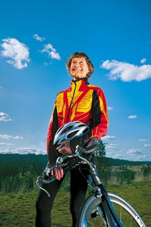 Mujer de la tercera edad recargada en una bicicleta, vestida deportiva