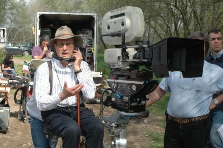 Director de cine sentado en un banco con personas y herramientas para grabar a su alrededor