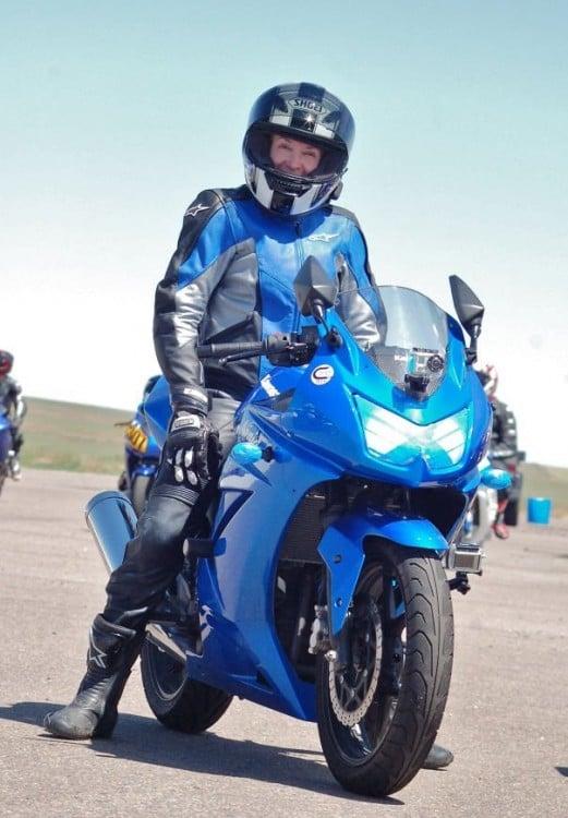 Mujer de la tercera edad sobre una motocicleta azul
