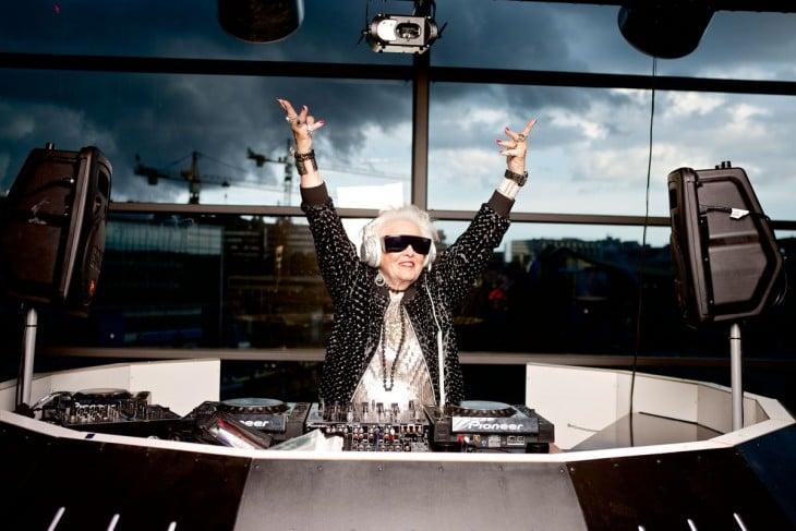 Mujer de la tercera edad dirigiendo una consola de DJ