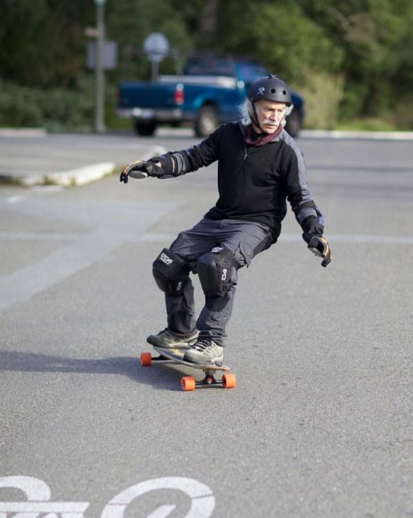 Hombre de la tercera edad en patineta por la calle