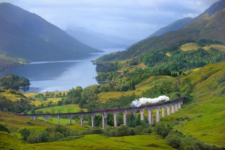 A lo lejos el tren El West Highlan Line en Escocia