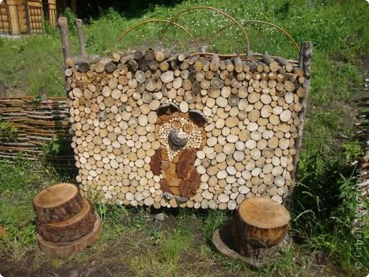 Pedazos de madera apilados que en el centro forman la figura de un pequeño oso