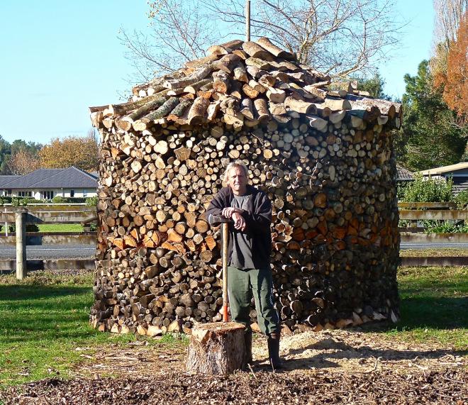 Hombre parado frente a una torre de troncos apilados en diferentes colores