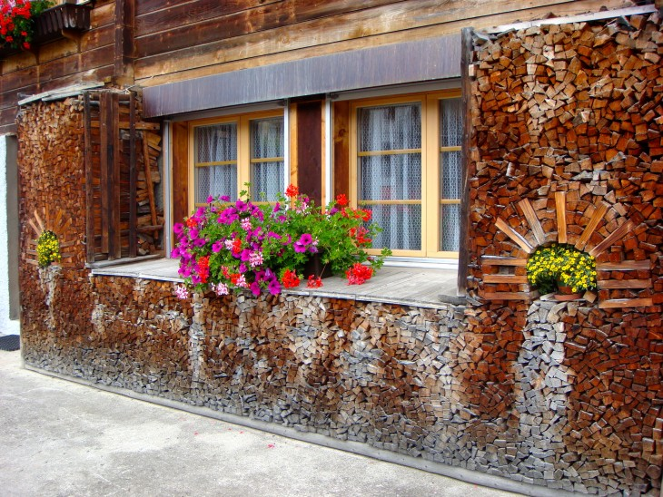 Pedazos de madera apilados de forma que rodean las ventanas de una casa con distintos colores