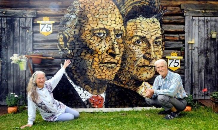 Dos personas sentadas en el piso mostrando una obra de arte formada con troncos que son las caras de estas personas