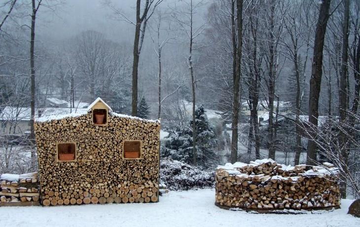 Troncos de madera juntos formando una pequeña casita con tres ventanas y un medio círculo en un cosatado