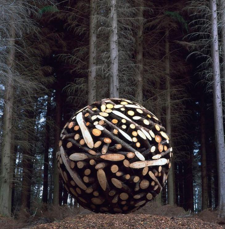 Pedazos de troncos formando una bola en un bosque frente a unos pinos