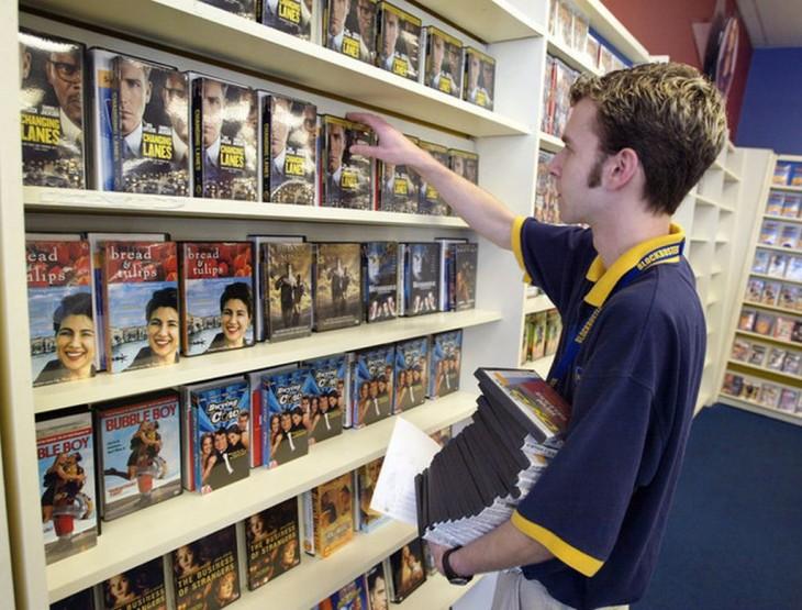 Empleado de Blockbuster acomodando películas