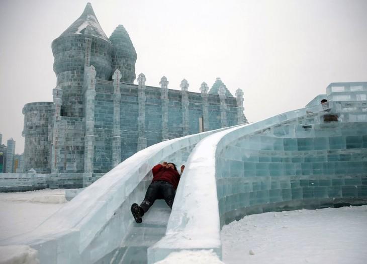 persona deslisándose por un tobogán hecho de hielo