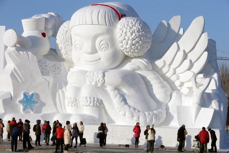 escultura de un niño sentado hecha con nieve y siendo observada por personas
