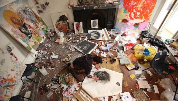 persona en el suelo dibujando un cuadro con pinturas a su alrededor