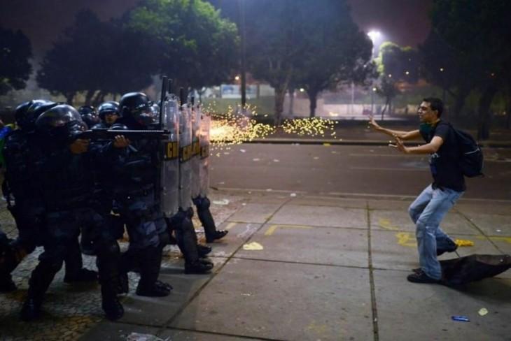 hombre frente a policías pidiendo paz