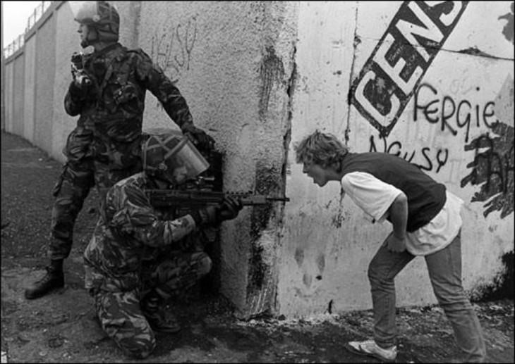joven gritandole a un soldado mientras este le apunta con su arma