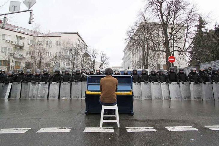 hombre tocando el piano frente a policías