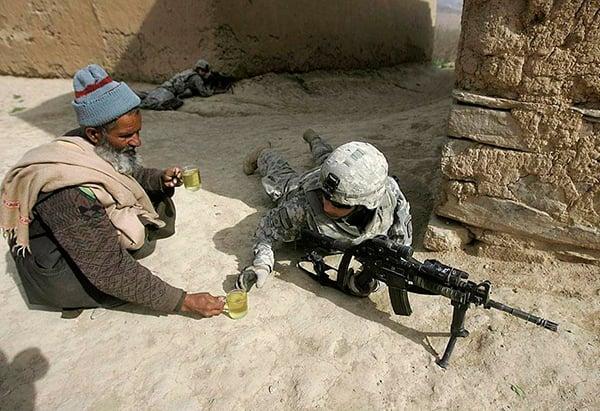 hombre dándole una taza de té a un soldado en la guerra