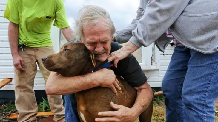 hombre abrazando a sus perro luego de encontrarlo en los escombros de una casa en ruinas