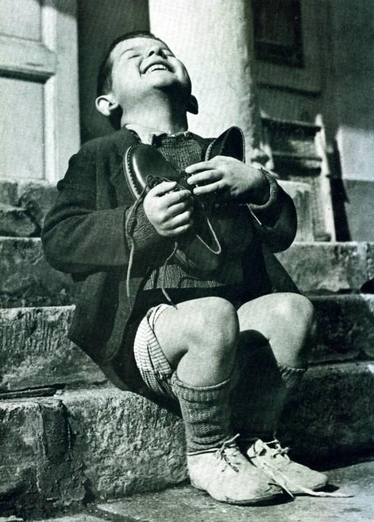 niño sosteniendo un par de zapatos en su pecho mientras se muestra emocionado y ríe
