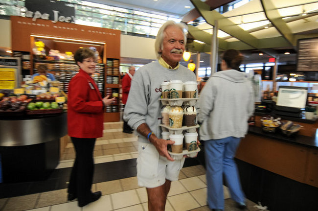 hombre cargando bandejas de café y caminando hacia la calle