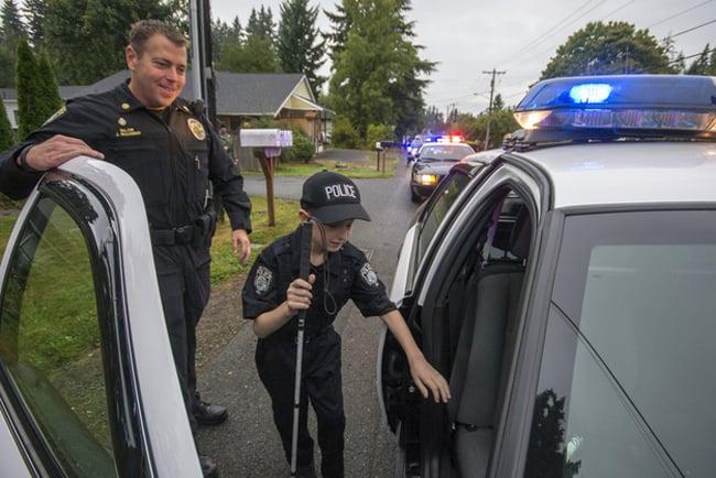 niño vestido de policía es acompañado por un oficial de policía a subir en una patruya