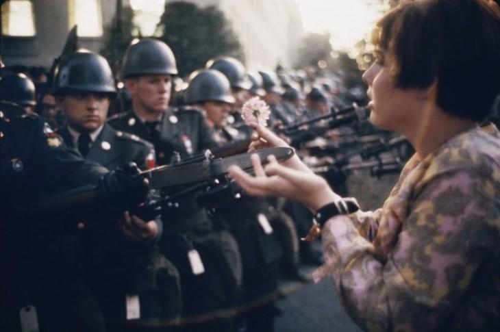 joven coloca una flor sobre los rifles de policías durante la guerra