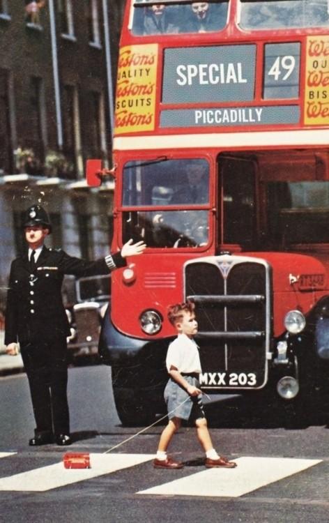 niño cruzando la calle y jalando un autobús de dos pisos mientras un oficial detiene el tránsito