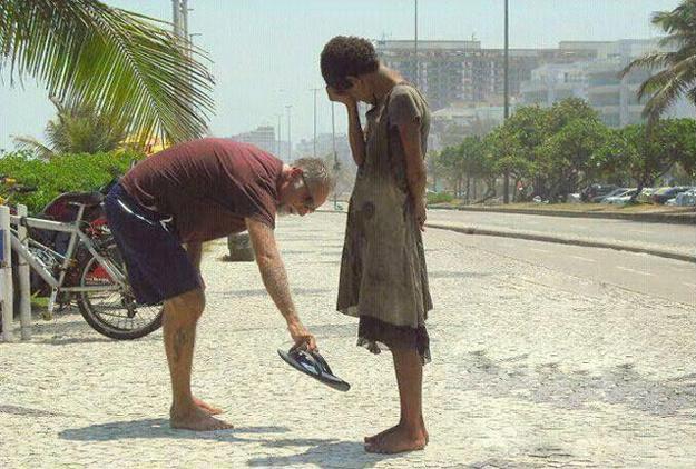 hombre entrega sus sandalias a una mujer indigente que esta en la acera