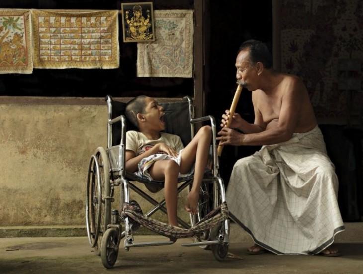 niño con discapacidades disfrutando de la música producidada por una flauta