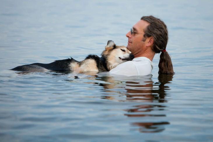 hombre sosteniendo a un perro dentro de un lago