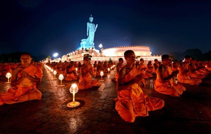 monjes budistas orando en medio de una plaza