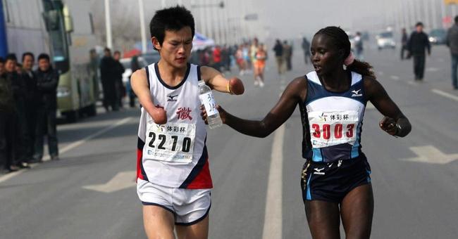 corredora de maratón ayuda a su compañero dándole agua para que llegue a terminar la carrera