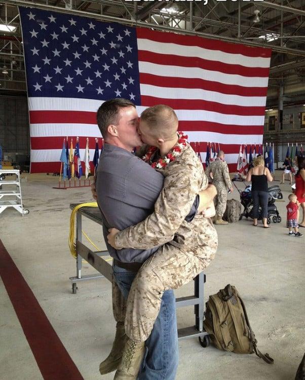 soldado besando a su novio con la bandera de estados unidos tras ellos